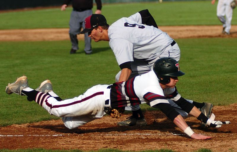 by: DAN BROOD - EFFORT -- Tualatin senior Joey Fishback is tagged out by Glencoe first baseman Trevor Williams as he dives toward first base after putting down a sacrifice bunt in Friday's game.