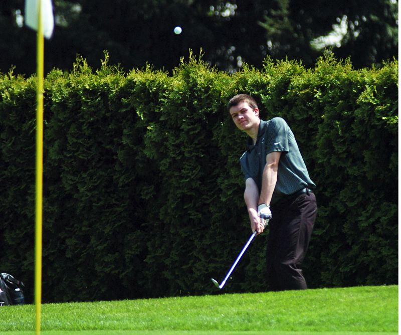 by: DAN BROOD - NICK CHIP -- Tigard High School senior Nick Jones chips onto the green on hole No. 12 during Monday's Pacific Conference tournament held at Tualatin Country Club. Jones had a round of 78.