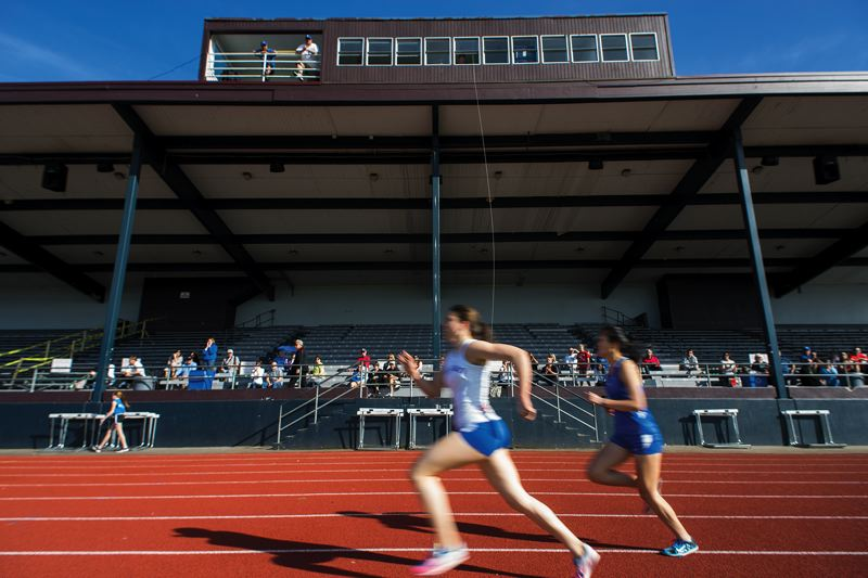 by: HILLSBORO TRIBUNE PHOTO: CHASE ALLGOOD - Runners pass in front of the grandstand at Hare Field in Hillsboro. The upper rows of the grandstand will be off-limits until the school district can renovate the structure this summer.
