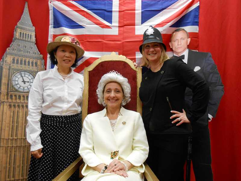 by: REVIEW PHOTO: JILLIAN DALEY - Volunteers, from left, Karen Chi (tea steward), Cherie Bates (the Queen of England) and Mendy Miller (police officer) pose as characters during the Culture Travels event at Lake Grove. Daniel Craigs cardboard likeness also made an appearance.
