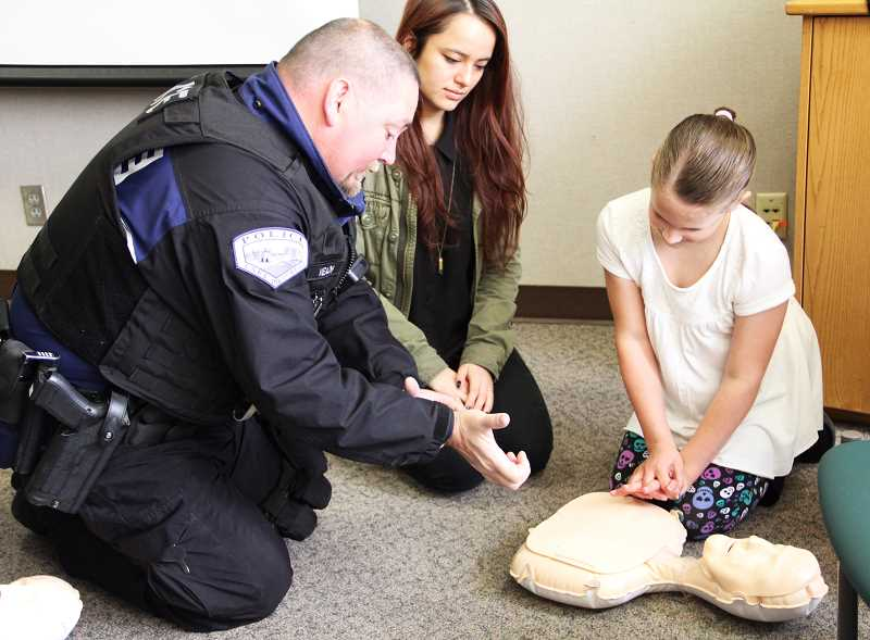 by: SUBMITTED PHOTO: CYDNY FLETCHER - Madalyn Boscacci practices CPR techniques under the expert guidance of LOPD Officer Denton Veatch and Emily Liu, assistant coordinator of the Lake Oswego Youth and Teen Program.