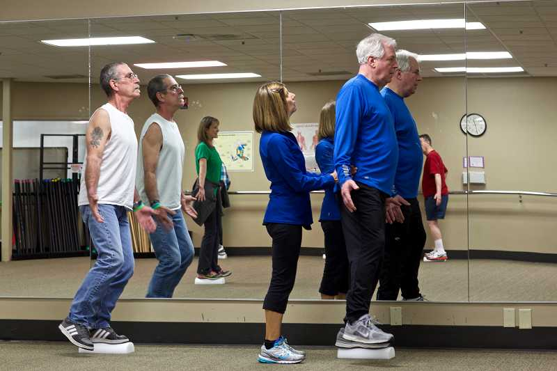 by: TIMES PHOTO: JAIME VALDEZ - Nancy Nelson helps clients balance on one foot during an exercise class in Lake Oswego on Friday. The classes are helping people with Parkinsons stave off some of the effects through exercise and movement.