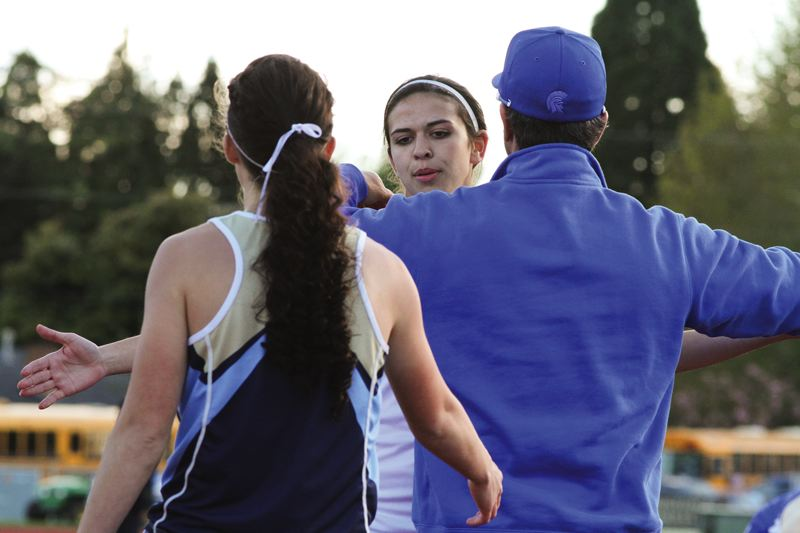 by: HILLSBORO TRIBUNE PHOTO: AMANDA MILES - Hilhi's Sami Moellmer gets a hug from a coach after narrowly losing to Liberty's Sarah Martinez (foreground) in the 400 meters last Friday.