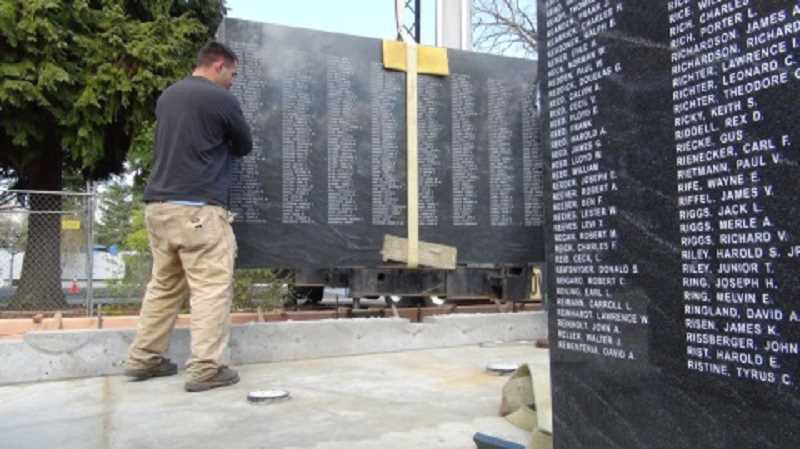 by: COURTESY OF OREGON DEPARTMENT OF VETERANS AFFAIRS - DELICATE WORK  - With the help of a crane, a worker moves a section of the Oregon WWII Memorial's wall into place before the obelisk is lowered onto its base.