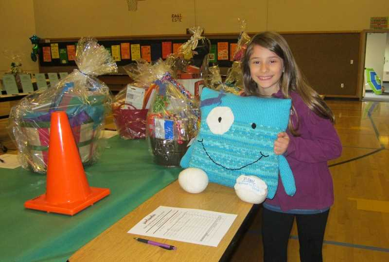 by: BARBARA SHERMAN - DETERMINED - Eliza Diforio hugs the pillow she hoped to win in a recent Deer Creek Elementary silent auction fundraiser; another family won the pillow, but the teacher who made it offered to sew another one for the auction, which Eliza won.