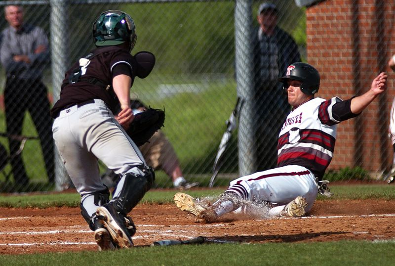 by: DAN BROOD - SAFE SLIDE -- Tualatin senior Cooper Brunner (right) is able to slide safely home before Tigard junior catcher Jarod Gogal can get over and make the tag in Tuesday's game.