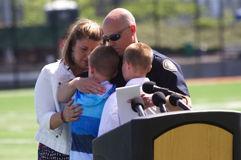 by: TRIBUNE PHOTO: JAIME VALDEZ - Portland Police Bureau Officer Jeff Dorn hugs his family wife Sarah and two sons, Mitchell, 12, and Jackson, 11, after Dorn said a spoke during a public tribute honoring the service of the bureau's canine officer, Mick, at Hillsboro Stadium.
