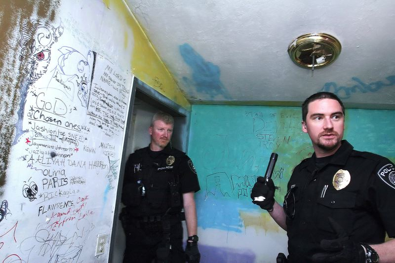 by: OUTLOOK PHOTO: JIM CLARK - Gresham police officers Jim Leake, left, and Dan Estes prepare to enter a deserted home on N.E. 181st Ave. that has been an ongoing problem in the area.