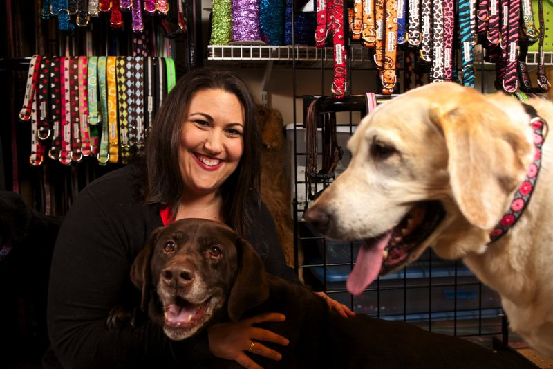 by: TRIBUNE PHOTO: JAIME VALDEZ - Murphy, a chocolate, and Bailey, a yellow Labrador, fashion dog collars that her owner, Kristine Smith, made at her home in Beaverton. Smith works at Nike and produces products for her Bark Boutique business in the evenings and weekends.