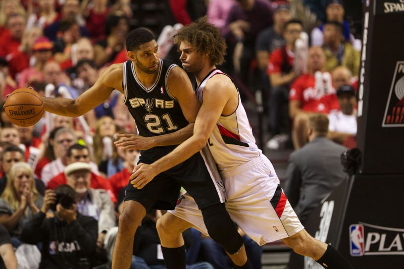 by: TRIBUNE PHOTO: JAIME VALDEZ - San Antonio's Tim Duncan meets Trail Blazers center Robin Lopez in a battle near the basket.
