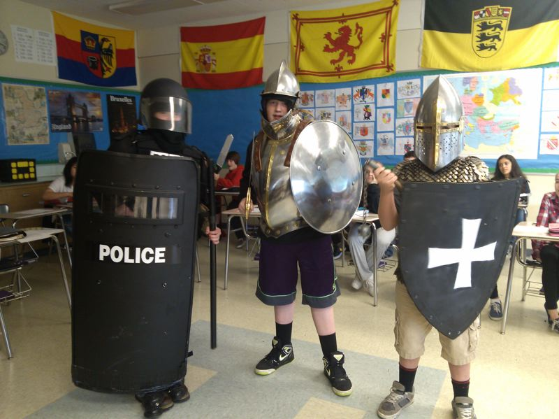 by: PHOTO BY: ULLI NEITCH/MILWAUKIE POLICE - Rowe Middle School students don modern police and medieval knight costumes as part of a lesson comparing the oaths of the organizations.
