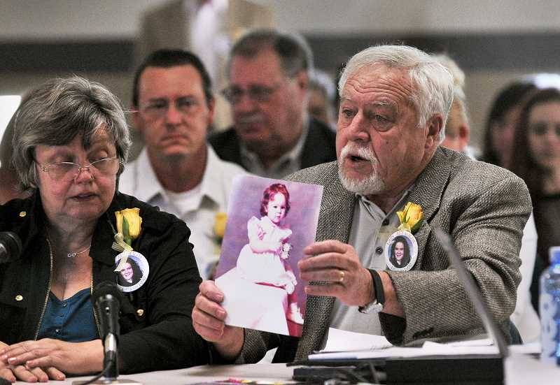 by: REVIEW PHOTOS: VERN UYETAKE  - Earl Reynolds shows the state parole board a photo of his daughter, Erin, as a baby while his wife Pam looks on. Erin was 16 when she was murdered by classmate Conrad Engweiler.