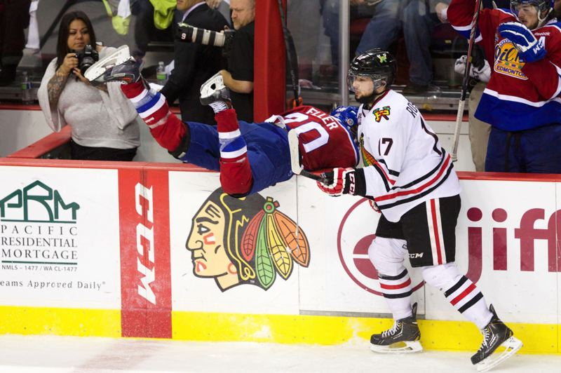 by: TRIBUNE PHOTO: JAIME VALDEZ - The Portland Winterhawks Adam Rossignol (right) helps the Edmonton Oil Kings Mads Eller over the barrier during the second period of Game 5 in the Western Hockey League finals.