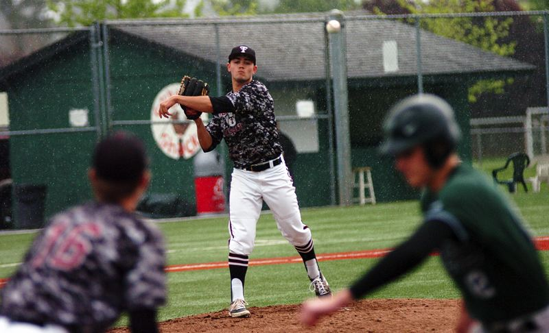 by: DAN BROOD - IN THE RAIN -- Tualatin senior Cooper Brunner makes a pickoff throw to first in Friday's game at Tigard.