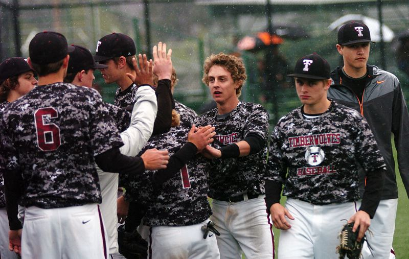 by: DAN BROOD - OUT IN FRONT -- Tualatin senior Joey Fishback is greeted by his Tualatin teammates after scoring a second-inning run in Friday's game.