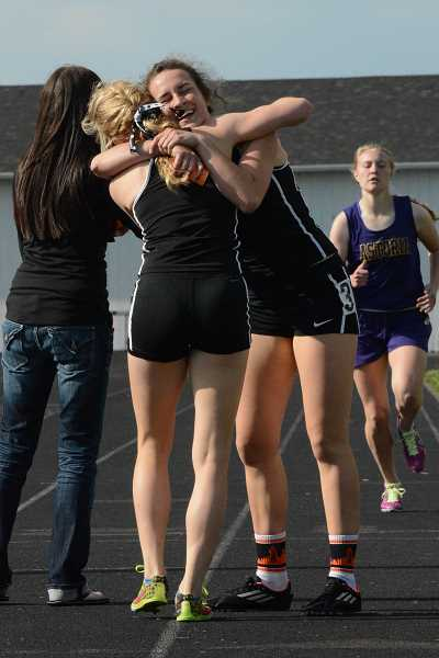 by: JOHN WILLIAM HOWARD - Seniors Charlie Davidson and Abby Kessi embrace after finishing first and second, respectively, in the girls' 800 meter final. Both will advance to the state championships in the 800 for the fourth consecutive season.