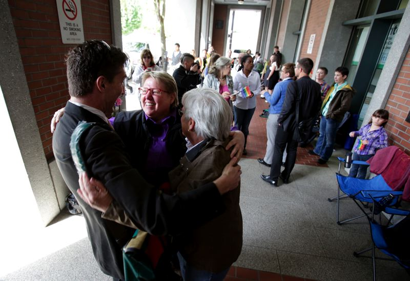 by: TRIBUNE PHOTO: JONATHAN HOUSE - Federal lawsuit plaintiffs Deanna Geiger and her partner Janine Nelson hugged their lawyer Monday morning while waiting for a marriage license in Multnomah County. A U.S. District Court judge struck down Oregon's ban on same-sex marriage in a 26-page ruling.