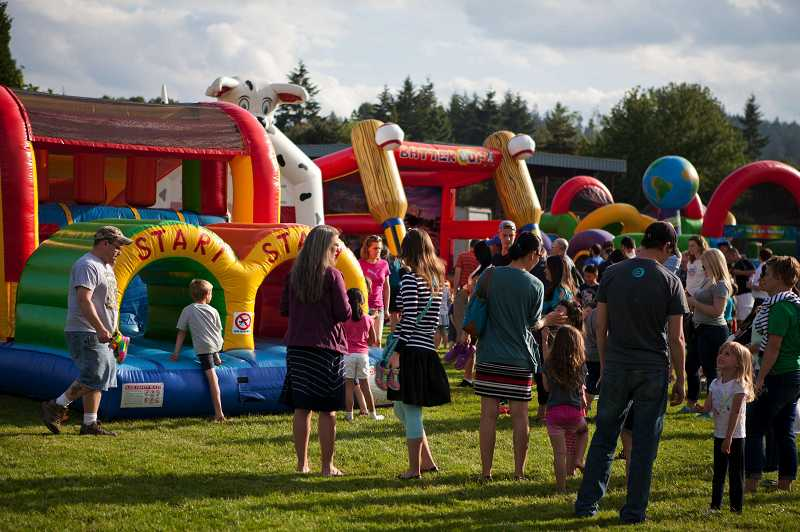 by: TIMES PHOTO: ADAM WICKHAM - Parents and children wait in line for the bouncy house.
