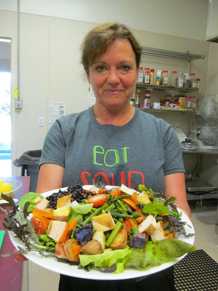by: PHOTO BY ELLEN SPITALERI - Josie Rankin-Lary, owner of Pepper & Salt, shows off a layered salad, with many local, organic ingredients.