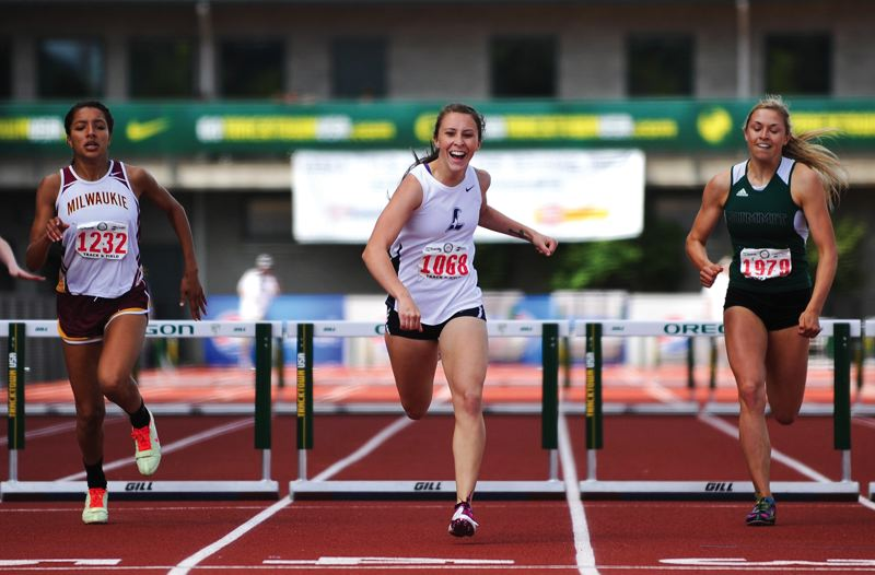 by: HILLSBORO TRIBUNE PHOTO: ZACK PALMER - Liberty senior Sarah Martinez breaks into a smile as she crosses the finish line in first place Saturday in the girls 300-meter hurdles at the Class 5A track and field state championships at Hayward Field in Eugene.