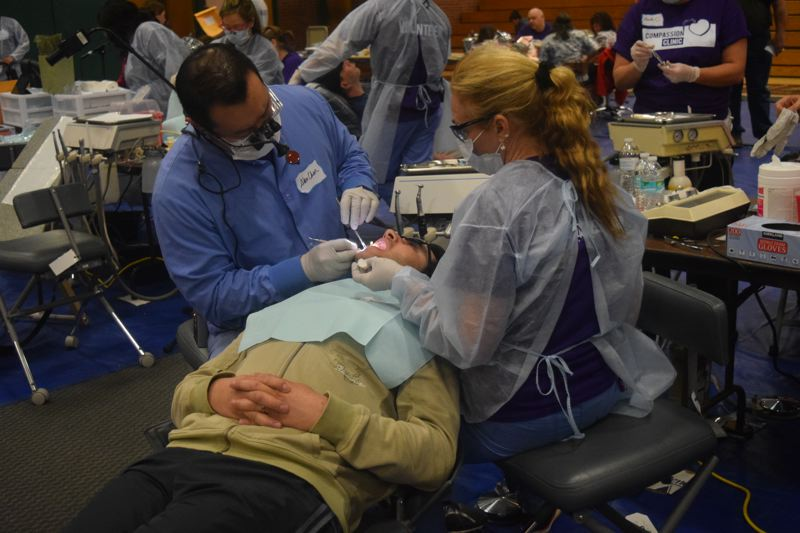 by: CONNECTION PHOTO: DREW DAKESSIAN - Volunteers perform dental work on a Compassion Southwest Portland guest free of charge.