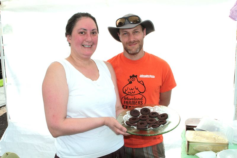 by: DAVID F. ASHTON - Mary Eastwood, the Cake Goddess - a former Vice President of the Sellwood-based Association of Home Businesses - offers samples to Moreland Farmers Market manager Adam Seidman.