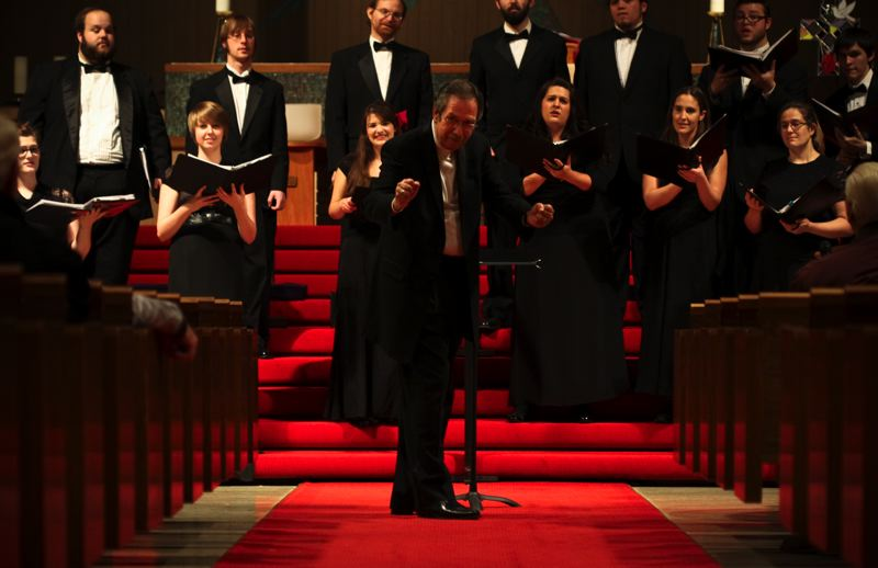 by: SUBMITTED PHOTO - Lonnie Cline, conductor and artistic director of Unistus Chamber Choir, conducts the group during a recent concert.