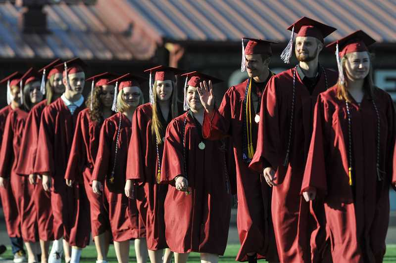 by: GAZETTE PHOTO: JOHN LARIVIERE - Sherwood graduates enter the Sherwood High School Stadium at the beginning of the 2014 commencement ceremony.