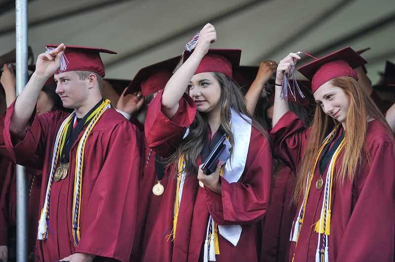 by: GAZETTE PHOTO: JOHN LARIVIERE - Sherwood Valedictorians Jacob Reimer (left), Rachel Bobelli (center) and Avery Rosenbaum (right) move their tassels from right-to-left as a symbol of officially graduating during the closing of the commencement ceremony.