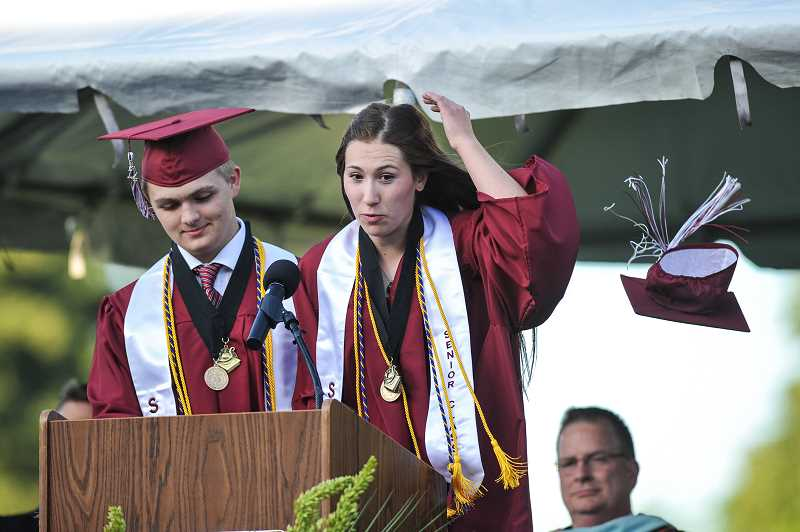 by: GAZETTE PHOTO: JOHN LARIVIERE - Hannah Zweig (right), Senior Class President, has a gust of wind blow off her cap during her welcoming comments shared with Ryan Ax, ASB President, at the beginning of the commencement ceremony.