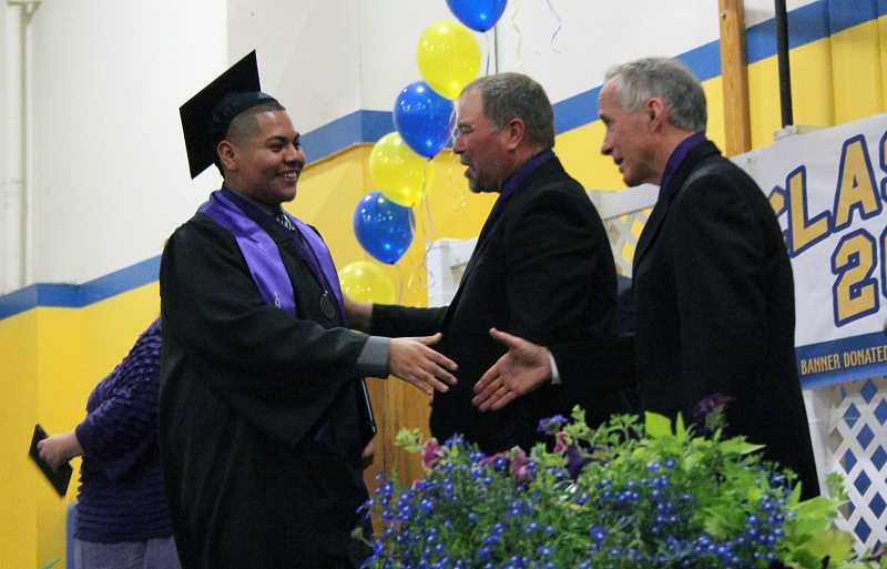 by: TYLER FRANCKE - Edwin Martinez (left) receives his diploma at graduation Saturday in Gervais High School from Gervais School Board Chairman Brent LaFollette and Superintendent Rick Hensel.