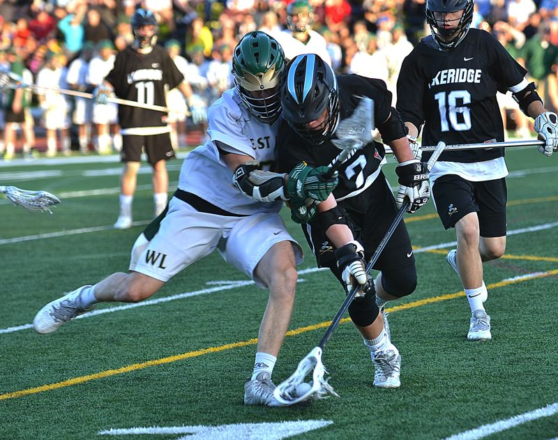 by: VERN UYETAKE - Laeridge's Joel Schwarz scoops up a ground ball during the state championship game at Lake Oswego High School Saturday.