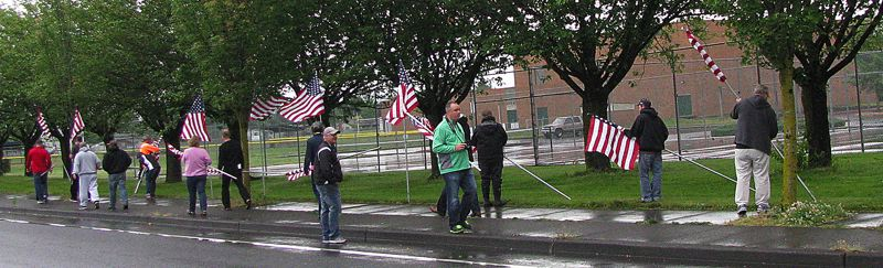by: OUTLOOK PHOTO: ANNE ENDICOTT - Reynolds High School teachers surround the school Friday morning, June 13, with American flags in observance of Flag Day, which is actually observed on Saturday, June 14.