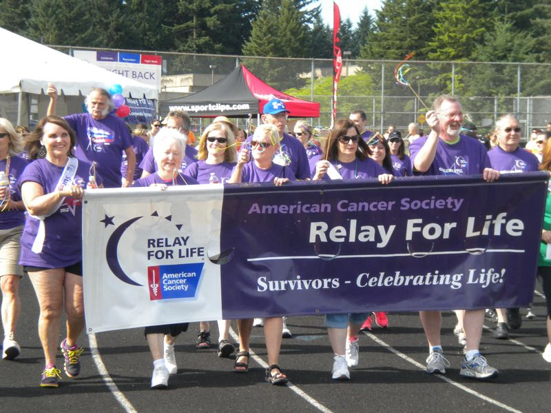 by: SUBMITTED PHOTO - Cancer survivors wearing special T-shirts walked the first lap at last year's Relay for Life in Oregon City.