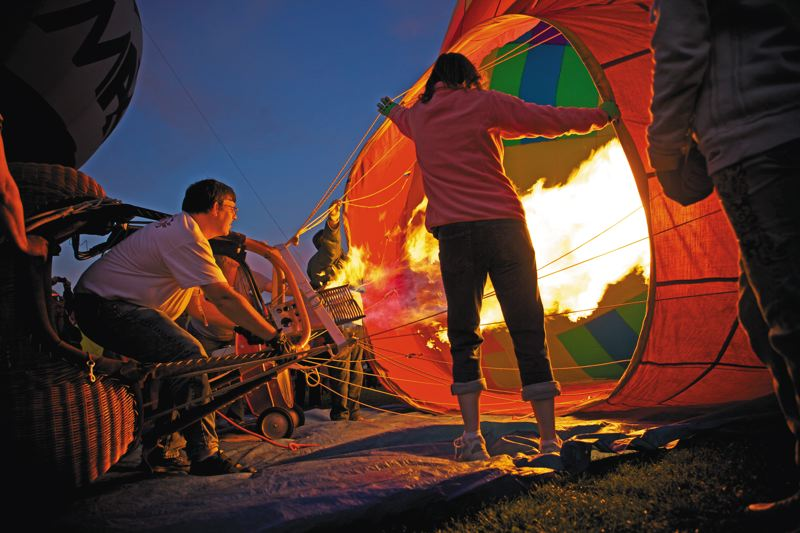 by: PAMPLIN MEDIA GROUP FILE PHOTOS - Firing up the hot air balloons can be an intense thing at the Tigard Festival of Balloons, especially at night (top), while colorful balloons dot the landscape at Cook Park (above). For info: tigardballoon.org.