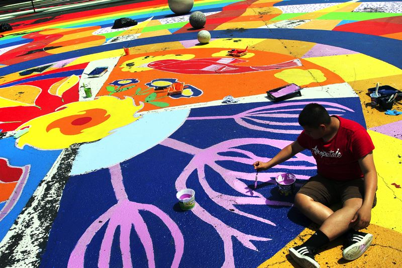 by: OUTLOOK PHOTO: JIM CLARK - Andy Acosta, 14, of Northeast Portland touches up the purple paint on the Plaza del Sol mural on Friday, June 20.