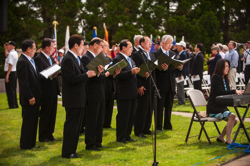by: SPOKESMAN PHOTO: JOSH KULLA - The Korean Elders Choir of Oregon performs June 21 at a commemoration in Wilsonville's Town Center Park to mark the start of the Korean War.