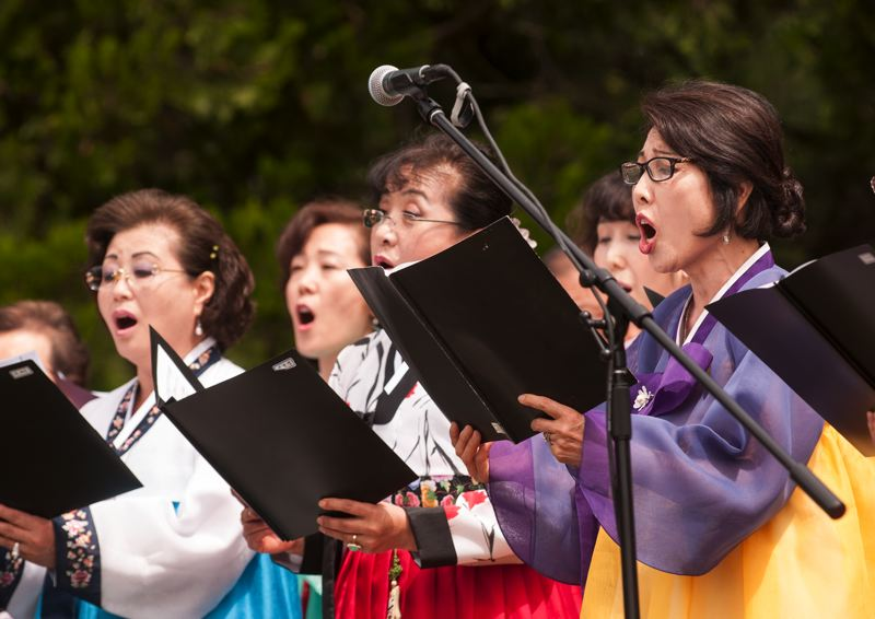 by: SPOKESMAN PHOTO: JOSH KULLA - The Korean Elders Choir of Oregon performs June 21 at Wilsonville's Town Center Park, part of a commemoration ceremony to mark the 1950 start of the Korean War.