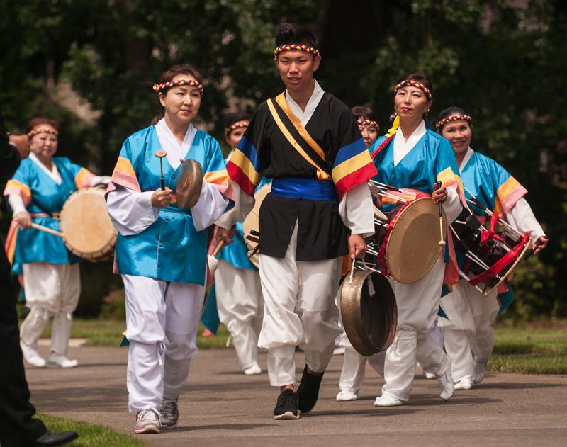 by: SPOKESMAN PHOTO: JOSH KULLA - Members of the Oregon Korean Culture Art Center's drum group perform June 21 at Wilsonville's Town Center Park.