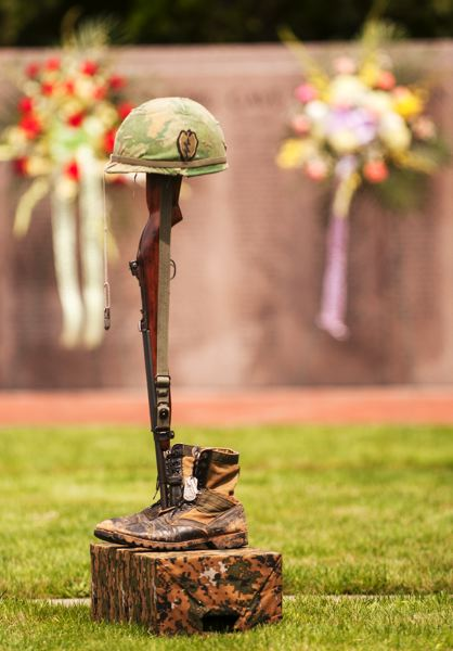by: SPOKESMAN PHOTO: JOSH KULLA - An M-1 carbine, combat boots and an old steel pot-style helmet commemorate the fallen of the Korean War during a June 21 commemoration at Wilsonville's Korean War Memorial.