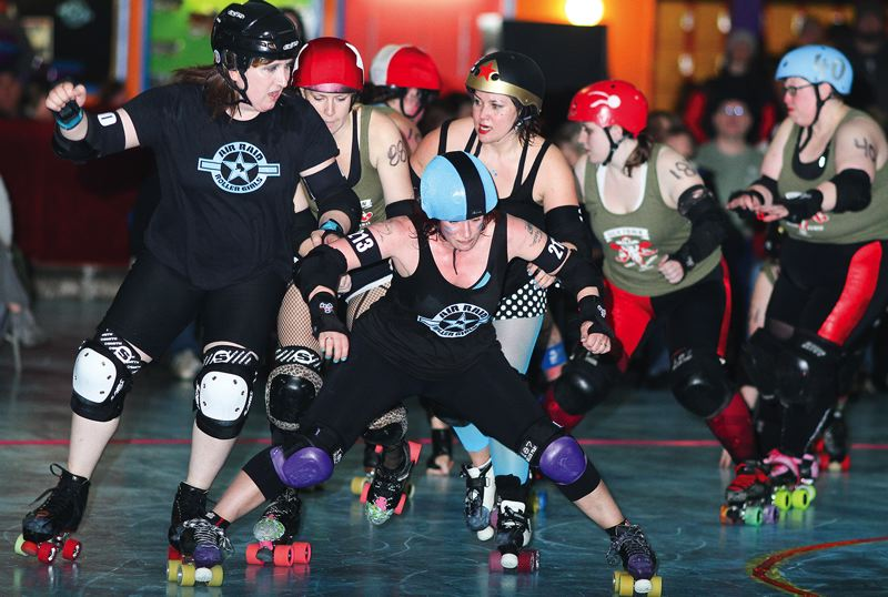by: HILLSBORO TRIBUNE PHOTO: CHASE ALLGOOD - The Hillsboro-based Air Raid Roller Girls battle for track position against the Sick Town Disorderlies during a roller derby match at Hillsboro Skate World earlier this season.