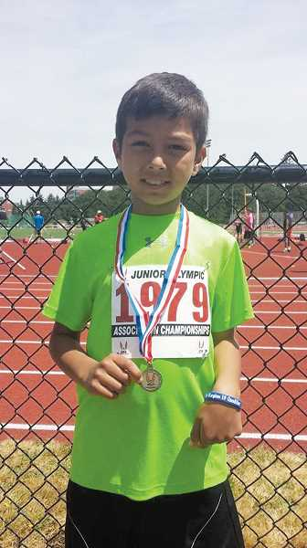 by: EVELING PARSONS - Seven-year-old Joaquin Parsons celebrates his Junior Olympic State Championship medal in the 400-meter-dash.