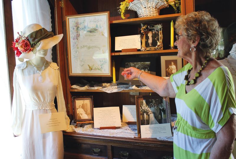 by: OUTLOOK PHOTO: CARI HACHMANN - Hybskman shares her familys wedding history, including her grandmothers floral-decorated wedding certificate from 1909. On the mannequin to the left, is a wedding dress worn in 1918 by the grandmother of local historian Sharon Nesbit.
