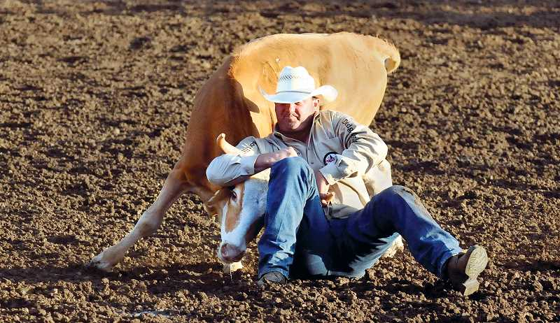 by: GARY ALLEN - Steer wrestling was one of many attractions available inside the rodeo grounds.