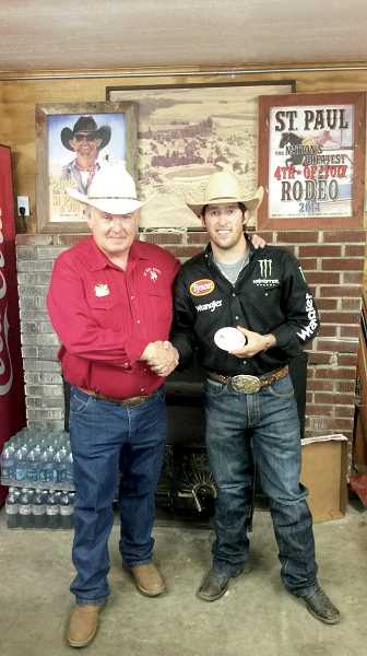 by: COURTESY OF ST. PAUL RODEO - St. Paul Rodeo board member Kevin Smith awards the PBR championship buckle to L.J. Jenkins. The Porum, Okla., cowboy is ranked 13th in the world and is headed to his tenth PBR World Finals this October in Las Vegas.
