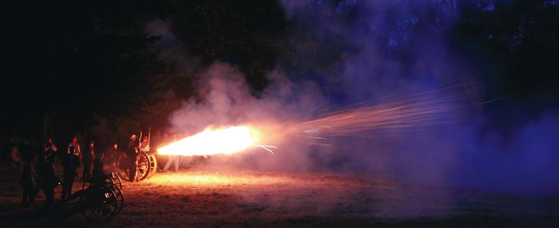 by: SUBMITTED PHOTO: STEPHEN YOUNG - After the public left on the Fourth of July, reenactors had their own fireworks show, involving shooting cannons in the dark.