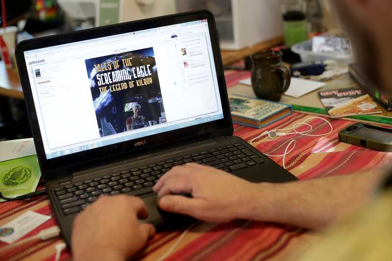 by: TIMES PHOTO: JONATHAN HOUSE - Aloha author Clayton Callahan checks out the Amazon listing of his ebook, 'Tales of Screaming Eagle, The Legend of Kilroy.'