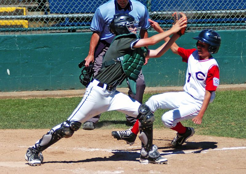 by: DAN BROOD - BIG PLAY -- Tigard catcher Nathan Ibarra grabs the ball to force out Cedar Mill's Ryan Ready at the plate during Sunday's District 4 Majors tournament game.