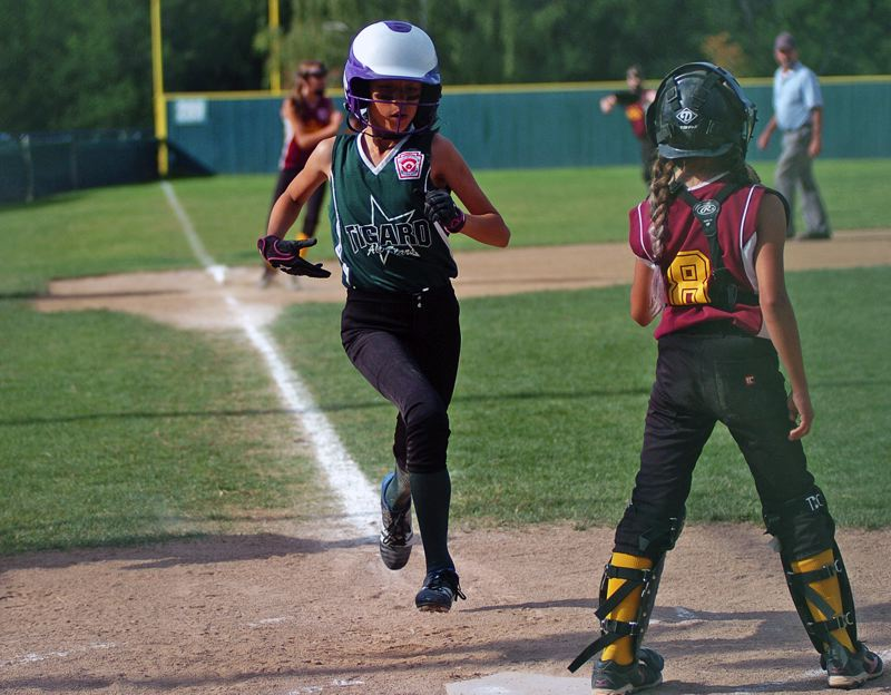 by: DAN BROOD - HEADING HOME -- Riley White (left) scores Tigard's first run during the District 4 title contest.