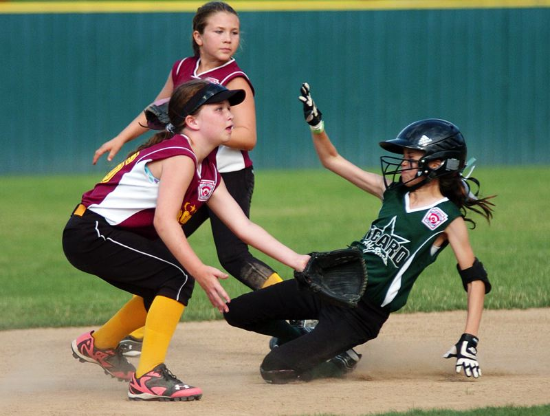 by: DAN BROOD - SAFE TO SECOND -- Tigard's Elli Dardis (right) slides safely to second base on a stolen-base attempt during last week's District 4 ages 10-11 tournament final. Tigard scored an 18-2 win over Forest Grove.